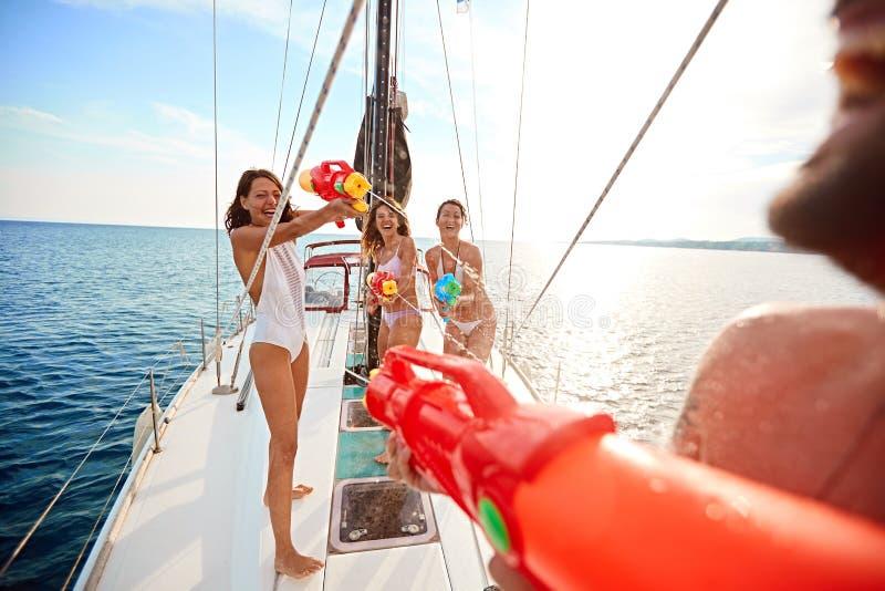 Os amigos jogam no barco de navigação com as pistolas de água em férias fotos de stock