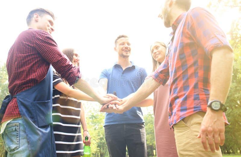 Os amigos juntam-se à mão junto durante no assado na natureza foto de stock royalty free