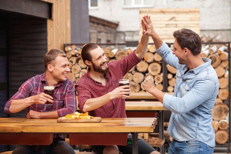 Os amigos masculinos consideráveis estão fazendo o divertimento no bar imagens de stock