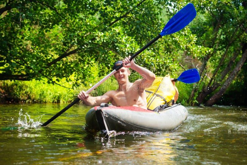Os amigos masculinos nadam no caiaque no rio selvagem no verão foto de stock royalty free