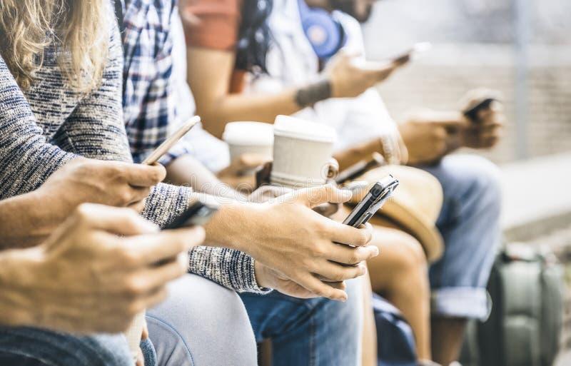 Os amigos multiculturais agrupam usando o smartphone com copo de café