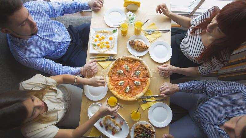 Os amigos novos encontram-se em um restaurante que comem o álcool bebendo da pizza e que dizem histórias fotos de stock
