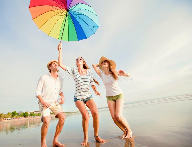 Os amigos novos felizes saltam com guarda-chuva colorido imagem de stock royalty free