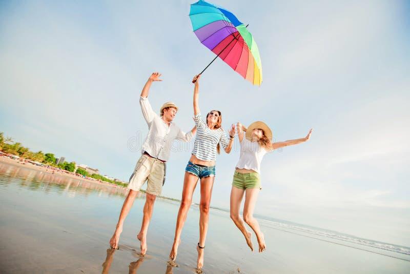 Os amigos novos felizes saltam com guarda-chuva colorido fotografia de stock