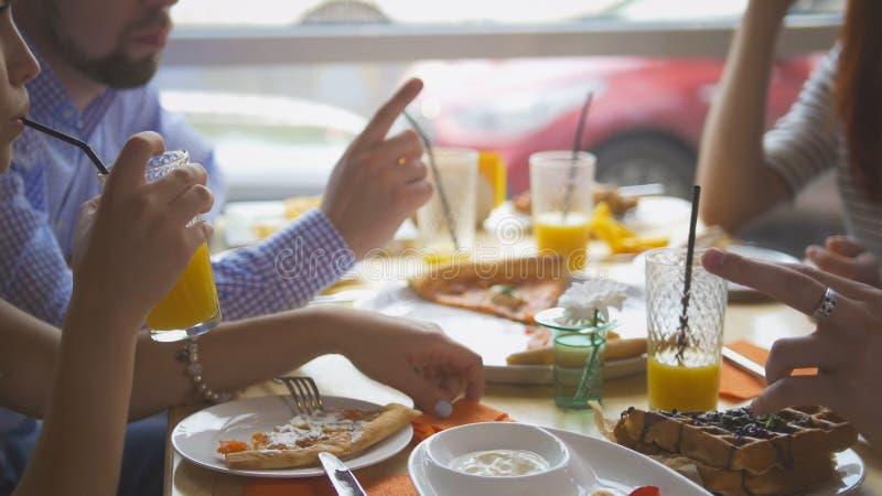Os amigos novos que tomam a pizza cortam da placa na tabela no restaurante fotografia de stock royalty free