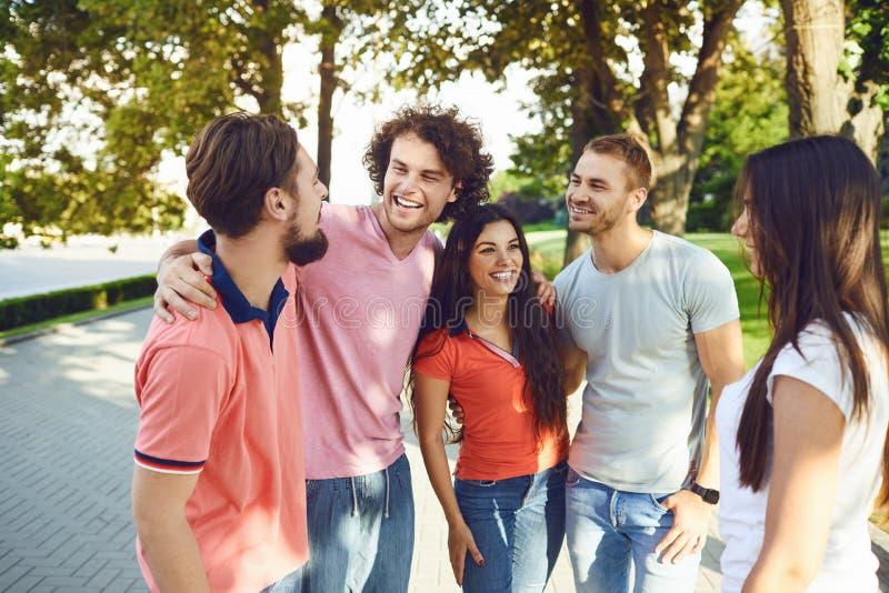 Os amigos novos têm o divertimento que falam na rua no verão imagem de stock royalty free