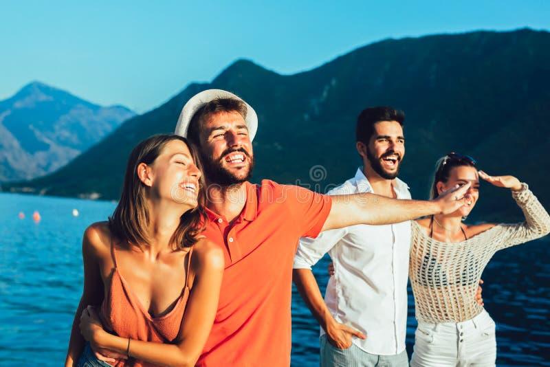 Os amigos que andam pelo porto de um mar tur?stico recorrem fotografia de stock