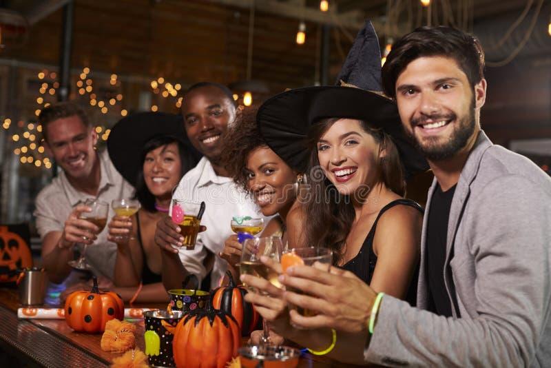 Os amigos que apreciam um partido de Dia das Bruxas em uma barra olham à câmera foto de stock royalty free