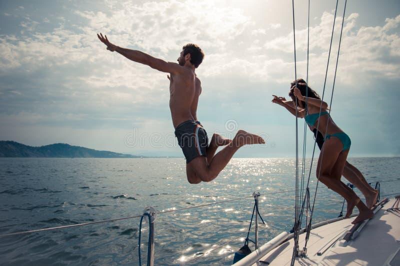 Os amigos que saltam na água de um barco de navigação fotos de stock
