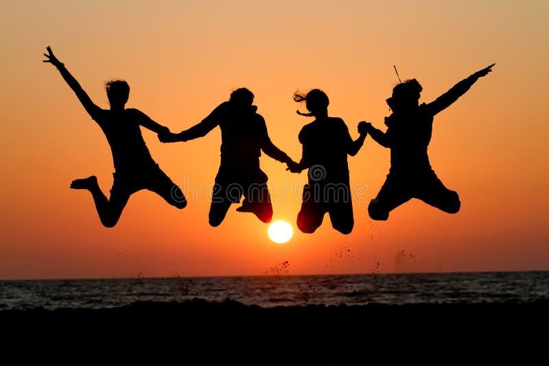 Os amigos que saltam no por do sol na praia imagem de stock royalty free