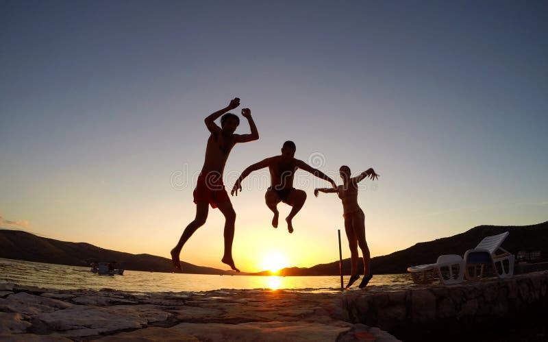 Os amigos que saltam no por do sol na praia foto de stock royalty free