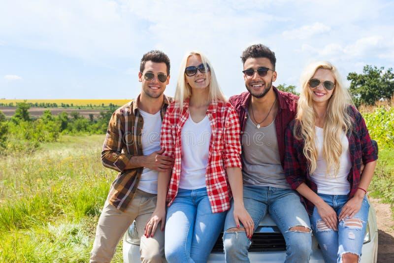 Os amigos que sentam-se em povos exteriores do campo do carro sorriem fotos de stock