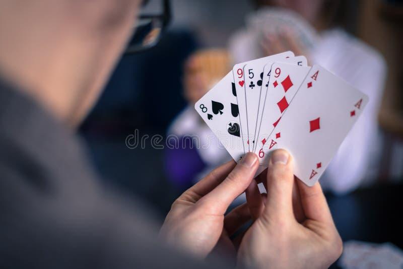 Os amigos são cartões de jogo junto em casa O homem está guardando os cartões em suas mãos, mulher no fundo obscuro fotografia de stock