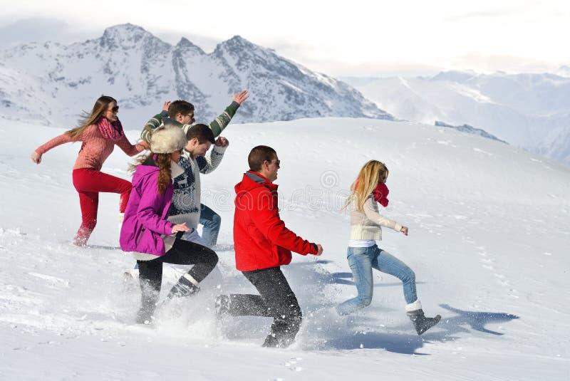 Os amigos têm o divertimento no inverno na neve fresca fotografia de stock