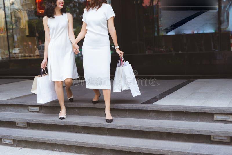 Os amigos vão comprar Caminhada de duas jovens mulheres no shopping com imagens de stock