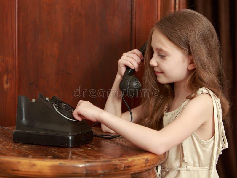 Os anéis da menina no telefone velho fotografia de stock