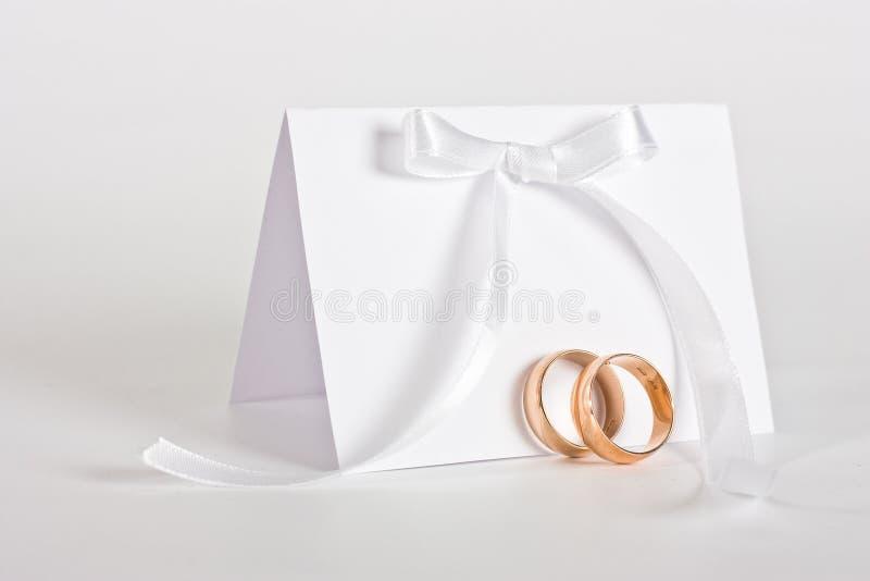 Os anéis de casamento e convidam com curva branca