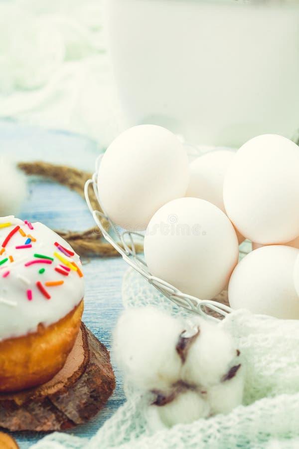 Os anéis de espuma com crosta de gelo em uma tabela branca, ovos brancos, menu do conceito da Páscoa, conceito da receita do rest imagem de stock