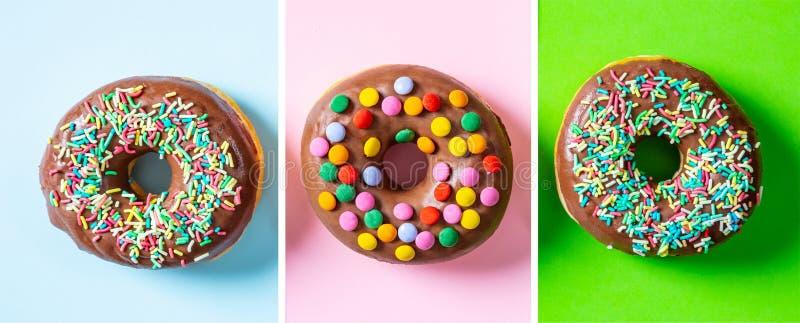 Os anéis de espuma com esmalte do chocolate, polvilham, três, vista superior e fundo verde cor-de-rosa isolado, azul fotos de stock royalty free