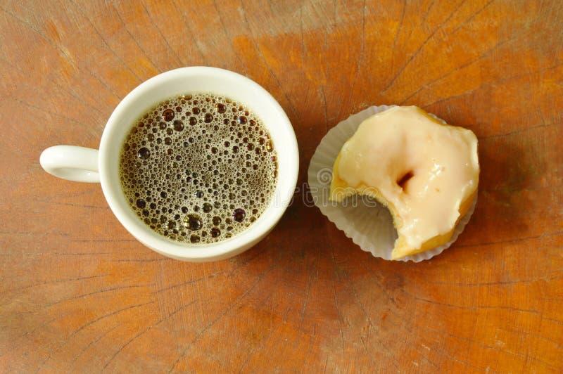 Os anéis de espuma de creme brancos mordem e o copo de café preto no fundo da placa de madeira foto de stock
