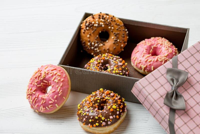 Os anéis de espuma deliciosos coloridos com polvilham em uma caixa em um fundo imagem de stock