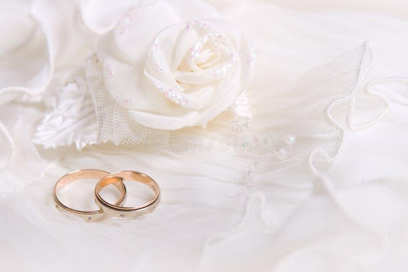 Os anéis e o branco de casamento levantaram-se fotos de stock