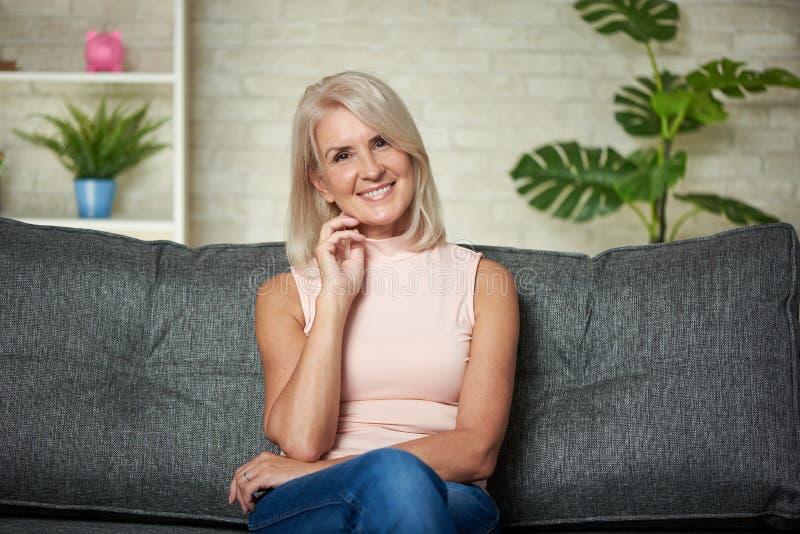 Os 50 anos bonitos da mulher estão sentando-se em um sofá em casa fotografia de stock royalty free