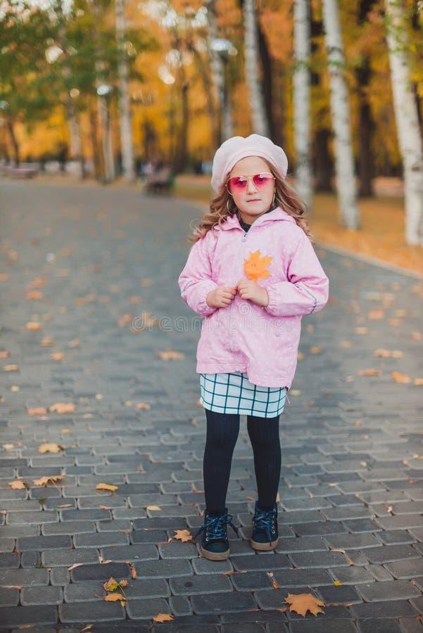 Os anos de idade à moda da menina 5-6 da criança que vestem o revestimento cor-de-rosa na moda no parque do outono olhando a câme foto de stock