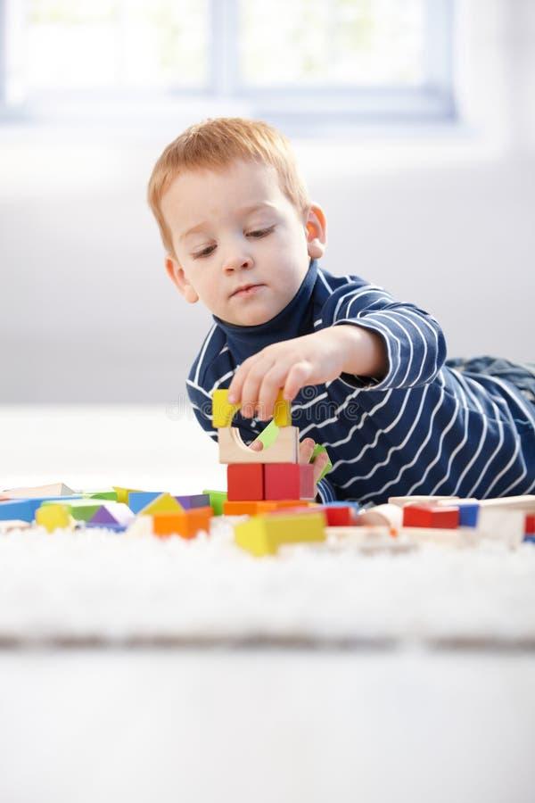 Os anos de idade 3 encantadores que jogam com cubos em casa fotos de stock royalty free