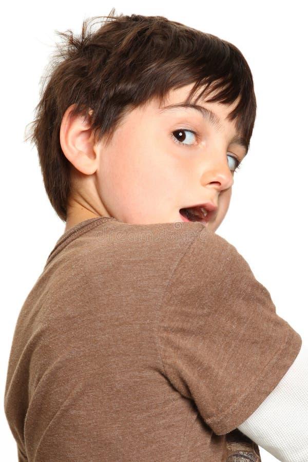 Os anos de idade sete que olham sobre o ombro fotos de stock
