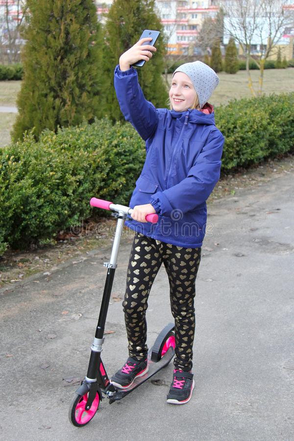 Os anos de idade de sorriso da menina 9-11 do preteen patinam no 'trotinette' e em tomar um selfie fora foto de stock royalty free
