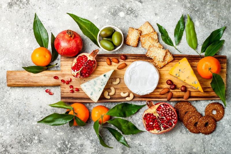 Os aperitivos apresentam com petiscos dos antipasti Placa da variedade do queijo sobre o fundo concreto cinzento Vista superior,  fotografia de stock