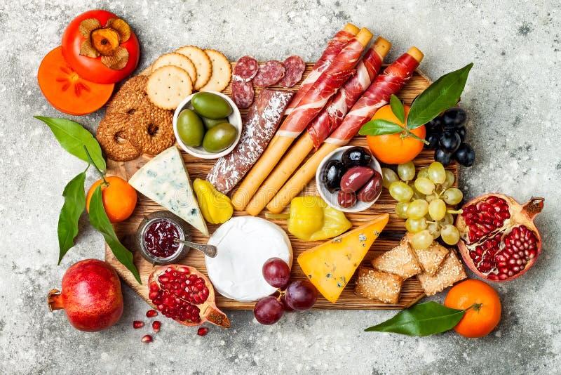 Os aperitivos apresentam com petiscos dos antipasti A variedade do queijo e da carne embarca sobre o fundo concreto cinzento Vist imagem de stock royalty free