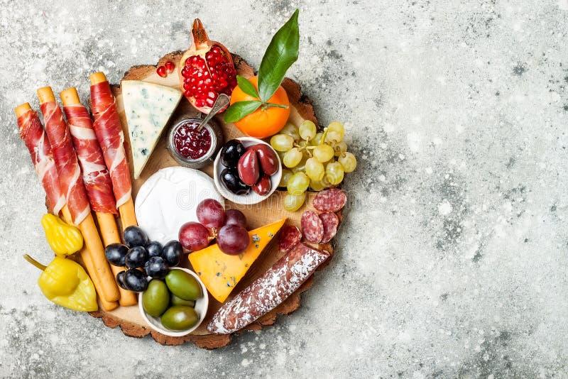 Os aperitivos apresentam com petiscos dos antipasti A variedade do queijo e da carne embarca sobre o fundo concreto cinzento Vist fotos de stock royalty free