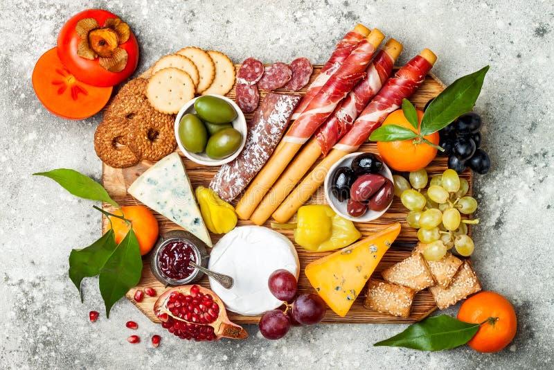 Os aperitivos apresentam com petiscos dos antipasti A variedade do queijo e da carne embarca sobre o fundo concreto cinzento Vist fotos de stock