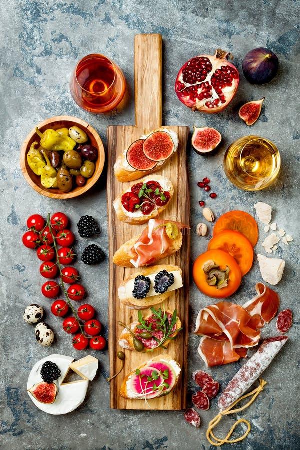 Os aperitivos apresentam com os petiscos e vinho italianos dos antipasti nos vidros Brushetta ou tapas espanhóis tradicionais aut fotos de stock