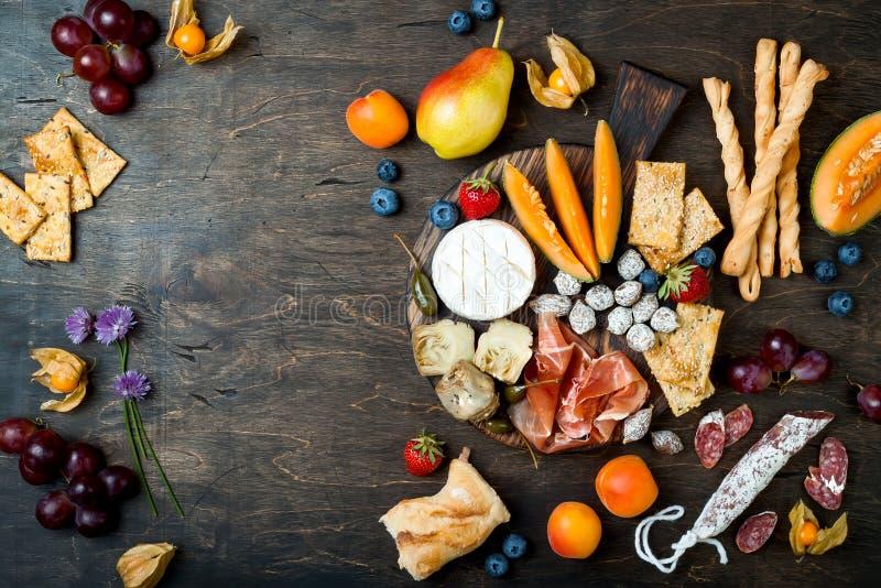 Os aperitivos apresentam com os petiscos italianos dos antipasti A variedade do queijo e do charcuterie embarca sobre o fundo de  imagem de stock