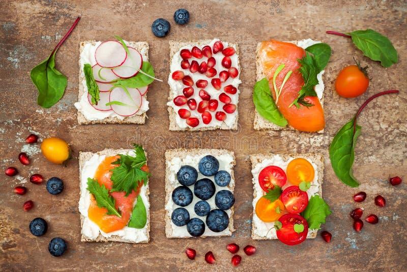Os aperitivos do crostini de Bruschetta misturam o grupo com as várias coberturas Variedade de sanduíches pequenos do café da man imagens de stock