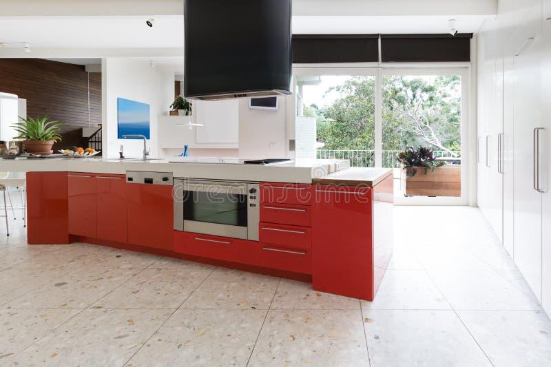 Os armários de cozinha do vermelho alaranjado na ilha bench em Aus luxuoso moderno fotografia de stock royalty free