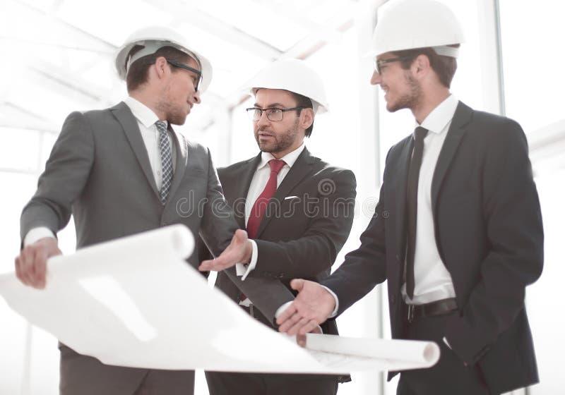 Os arquitetos mostram ao cliente um projeto de design novo foto de stock