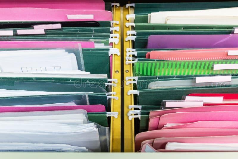 Os arquivos documentam de pastas de arquivos de suspensão em uma gaveta em uma pilha inteira imagens de stock