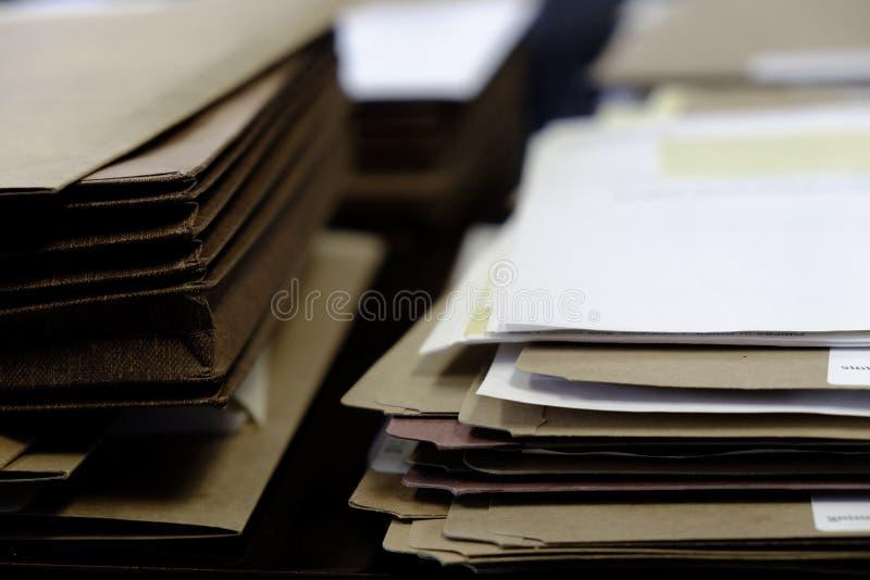 Os arquivos e os dobradores na mesa funcionam a informação ocupada imagem de stock