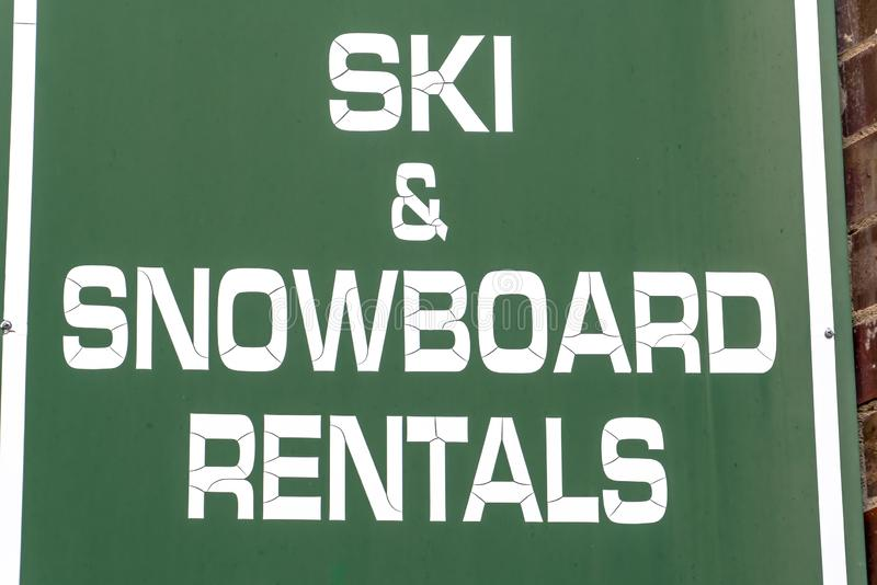 Os arrendamentos do esqui e do Snowboard assinam em uma estância de esqui foto de stock