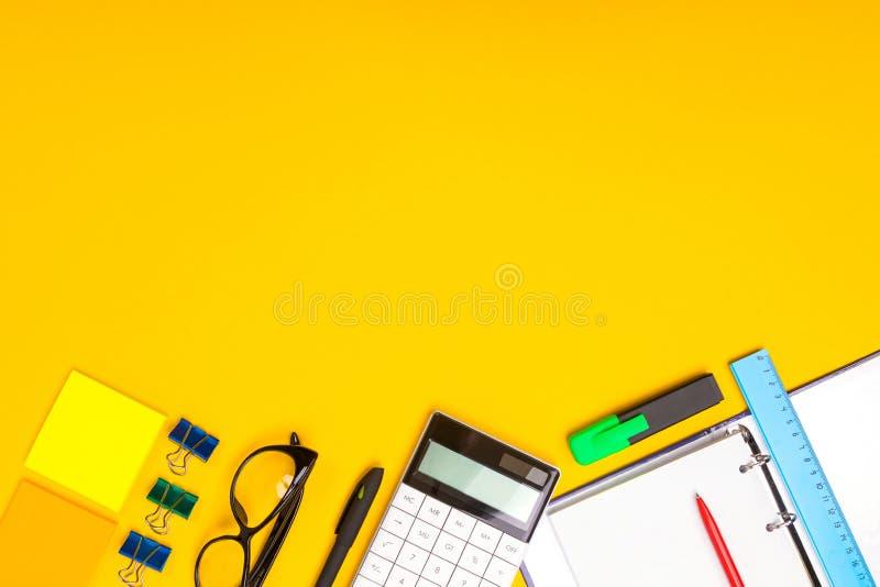 Os artigos de papelaria na parte inferior da imagem são isolados em um fundo amarelo imagens de stock royalty free
