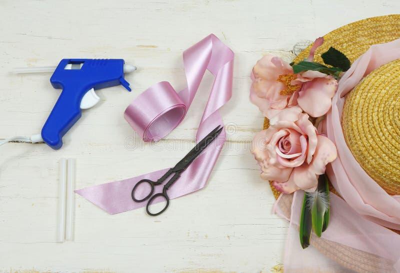Os artigos para decorar uma capota incluem um chapéu de palha, umas rosas do tesoura do vintage, as de seda e uma arma de colagem foto de stock royalty free