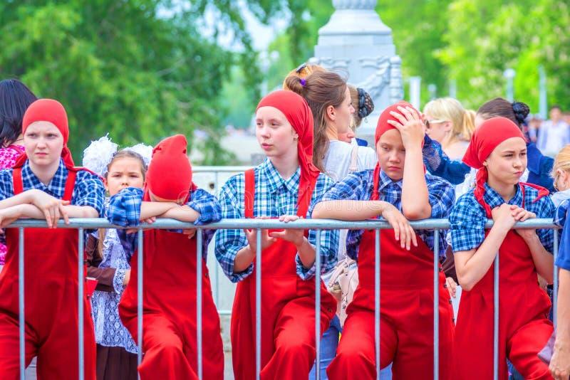 Os artistas do grupo do teatro em macacões e em scarves vermelhos participam na procissão festiva de graduados da High School imagem de stock royalty free