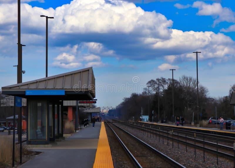 Os assinantes na plataforma da estação após o trem de Metra passam através de um estação de caminhos-de-ferro do ` s do subúrbio  fotos de stock royalty free