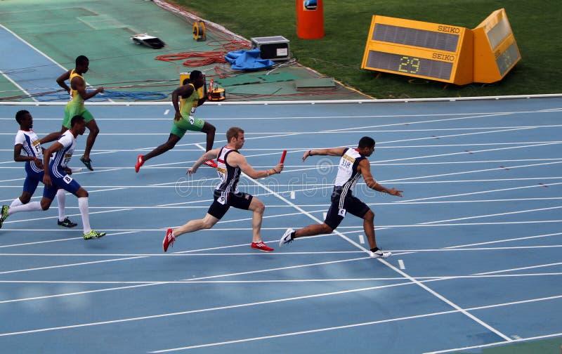 Os atletas competem na raça de relé 4x100 imagem de stock royalty free