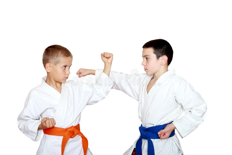 Os atletas das crianças no quimono executam o karaté das técnicas foto de stock