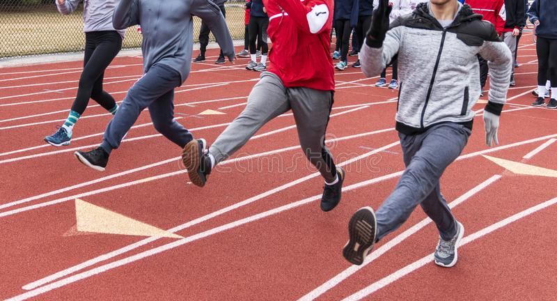 Os atletas que executam a corrida furam nas pistas em uma trilha vermelha no frio fotografia de stock royalty free